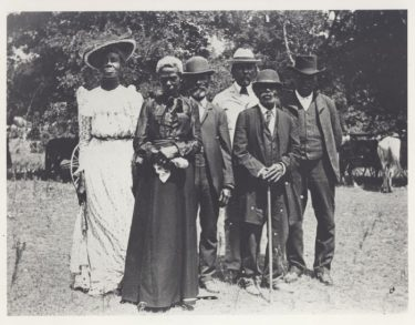 A group of people poses outside for this photo from 1900.