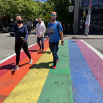 Four people walking across a rainbow painted crosswalk in Capitol Hill's Pike/Pine corridor.