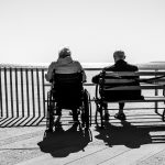 two elderly people sit on a bench