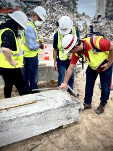 Four people in hard hats and bright yellow safety vests inspect a piece of concrete. Debris is piled up behind them.