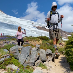 Two students are on a rocky with hiking poles and a glacier in the background.