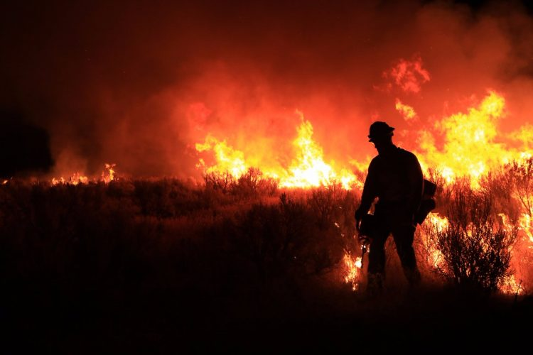 firefighter silhouetted against flames at night