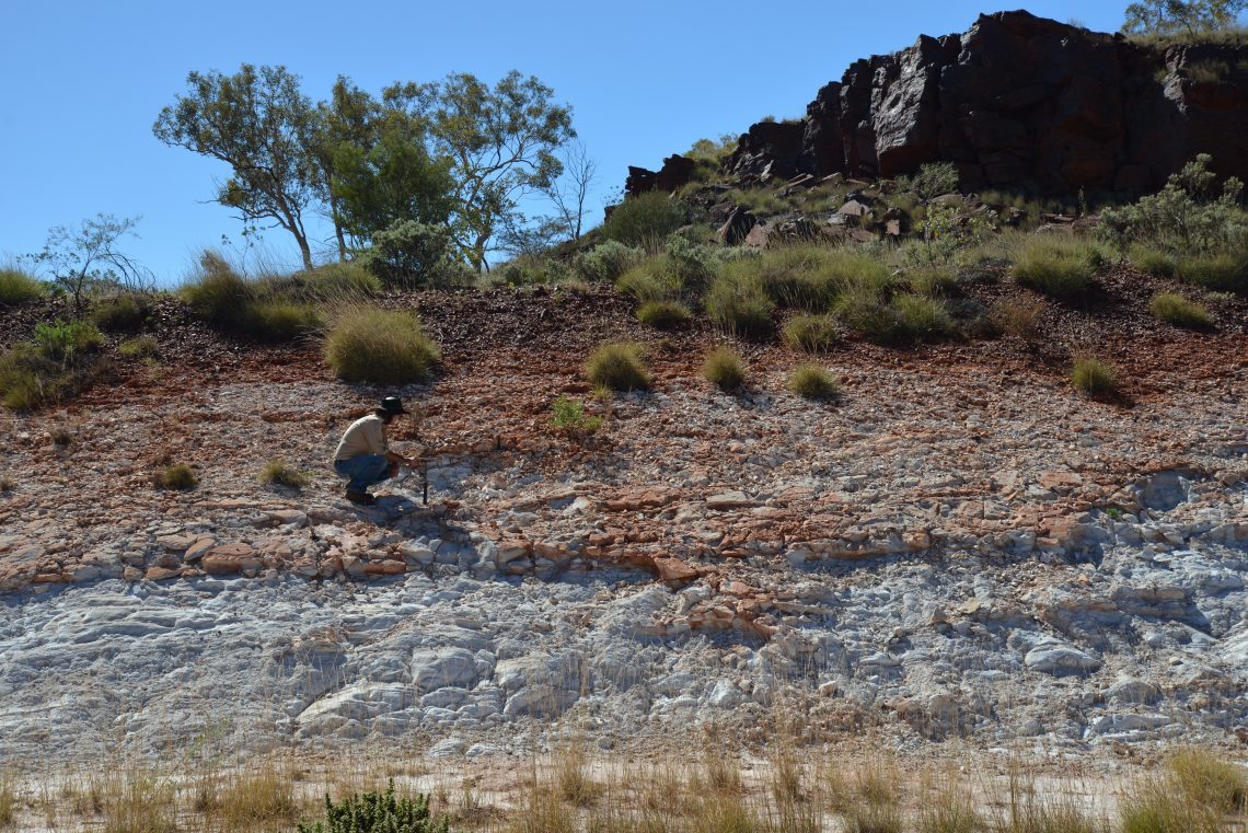 person crouching in distance on layered rock