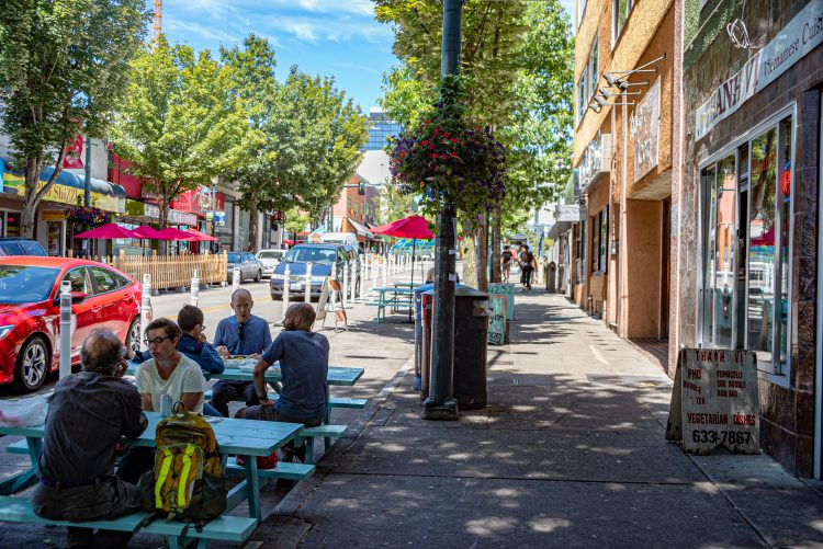 Restaurants, sidewalk and a lane of traffic reserved for tables. People sit at the tables.