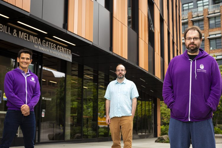 Three people stand outside in front of a building