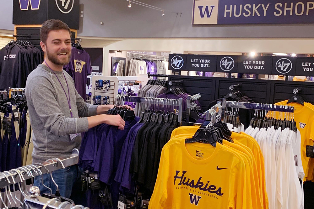 man looking through UW shirts at University of Washington Bookstore