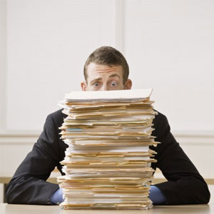 Man sitting behind a stack of file folders