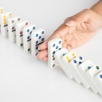 Concept image of a human hand stopping a line of dominoes from falling.