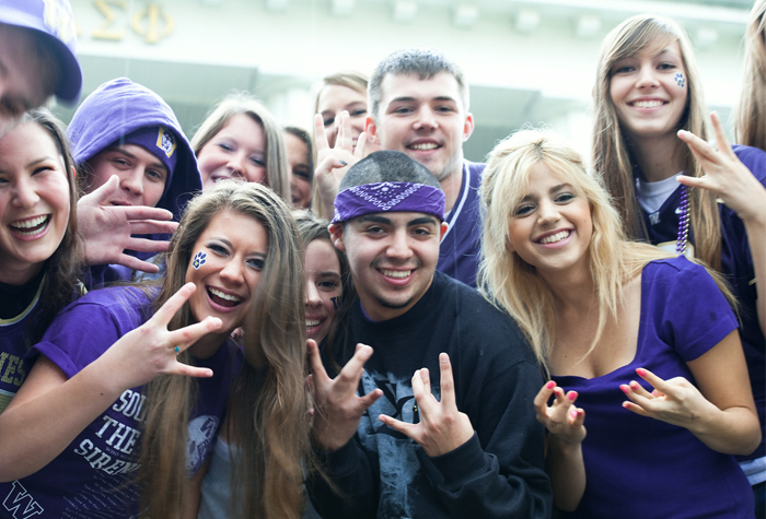 UW students dressed in purple making the w symbol with their fingers