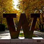 photo of bronze block W that stands at entrance to UW on NE 45th Street. In background is Memorial Way. Fall.