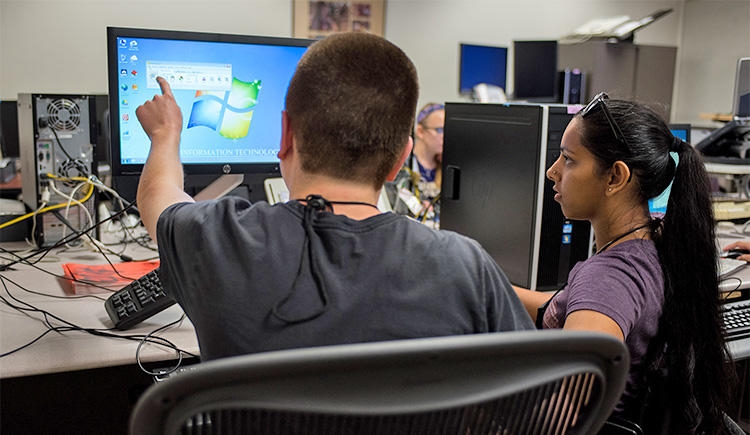 Two students work together in front of a computer screen using accessiblity tools.