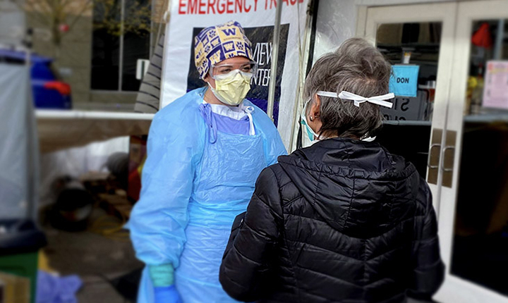 Medical person in scrubs and mask talking to another person wearing a mask.