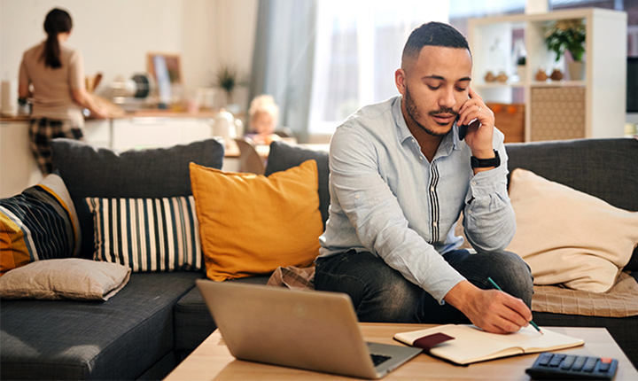 Portrait of modern mixed race man speaking by phone while working from home in cozy interior.
