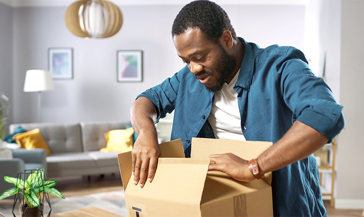 Man opening box containing a laptop.