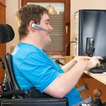 Man with spastic infantile cerebral palsy caused by a complicated birth sitting in a multifunctional wheelchair using a computer with a touch screen and wireless headset.