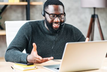 Man wearing headset while smiling and looking at a computer monitor.
