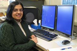 Gargi Chakraborty sitting in front of computer screens