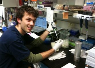 Nicholas Provine pipetteing in lab