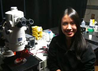 Leticia Huynh sitting in front of microscope