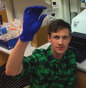 Evan Boyle examining microscope slide