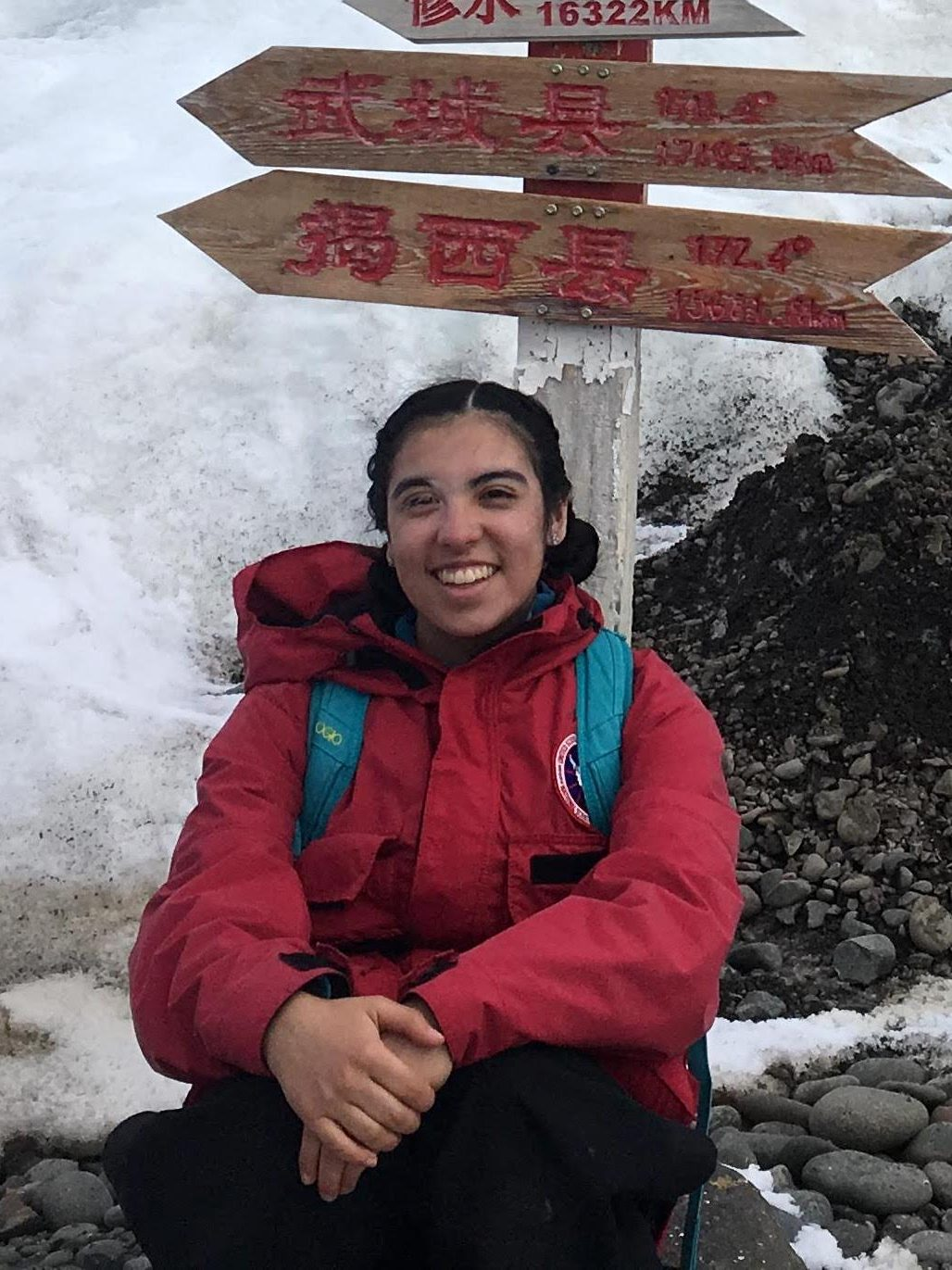 Sofía in front of hiking sign, smiling