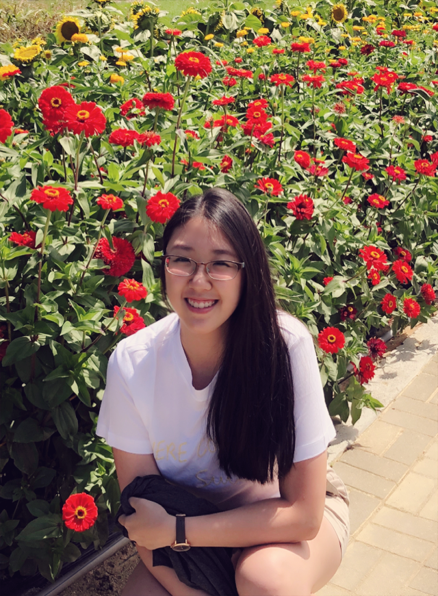 Min Su Kim smiling in front of a bed of roses