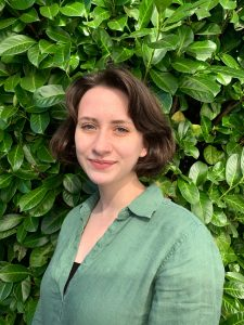 Gwen in front of a leafy bush
