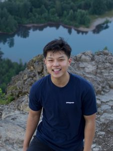 Tai smiling in front of a lake