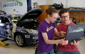 One woman and man looking at a laptop in an automotive lab