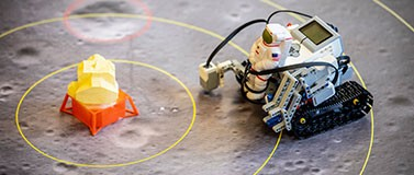 A Lego Mindstorms robot, with a plastic astronaut strapped to the front, approaches the lunar lander. Student teams will program the robot to explore the moon's surface.