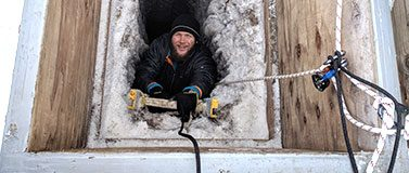 Oceanography graduate student Zac Cooper climbs down an icy ladder into the tunnel in May 2018. Researchers are harnessed to a rope for safety.
