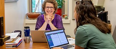 Emily M. Bender meets with a student in her office. Since she first offered her Ethics and Natural Language Processing course, ethics topics have been added to courses across the department's computational linguistics curriculum.