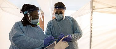 Two nurses wearing protective clothing refer to a clipboard.