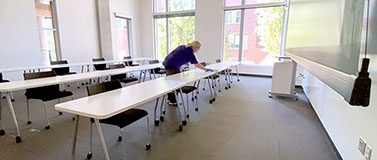 A person cleans a row of desks in a classroom