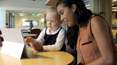 Victoria Chambers teaches a young girl how to use the motion-sensing software she helped develop last summer at MultiModal Health.