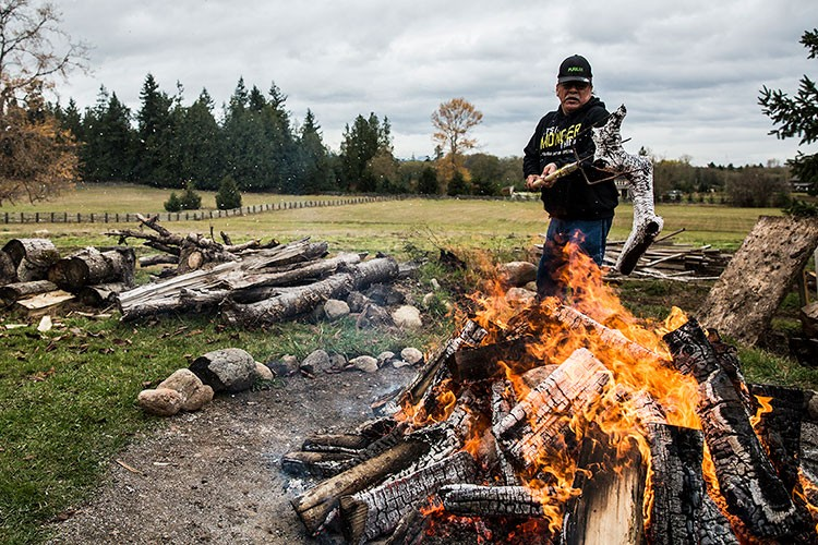 A man builds a fire in a rural area.