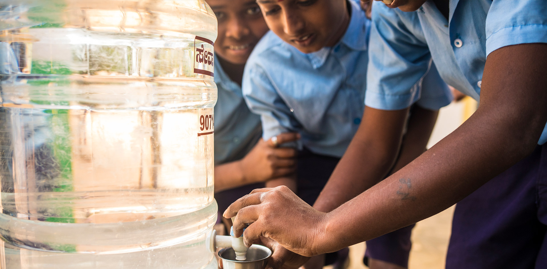 Schoolboys fill their cups with clean drinking water