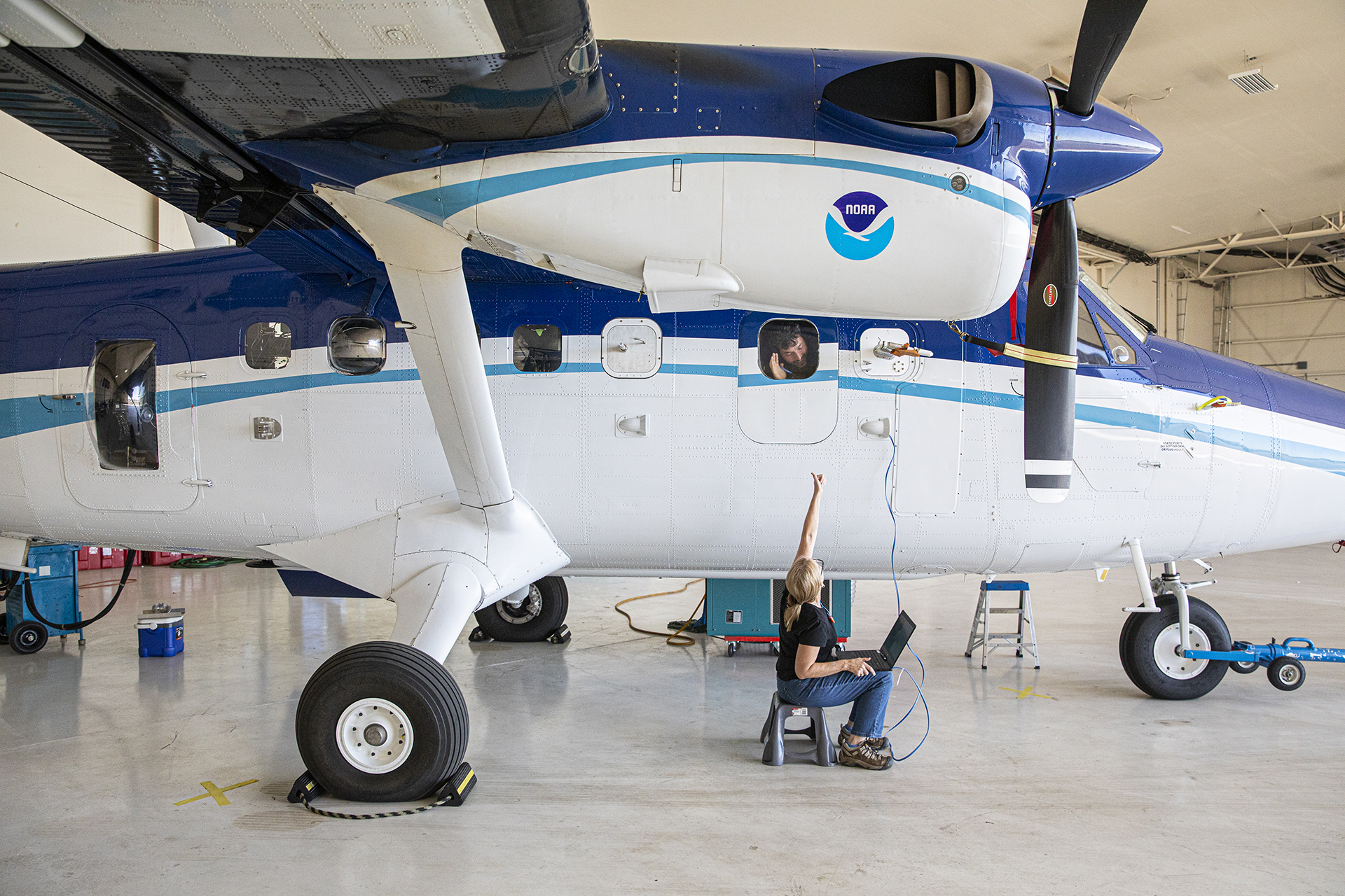 NOAA researchers Anne Middlebrook is seated under the plane and Alessandro Franchin is in the plane window.