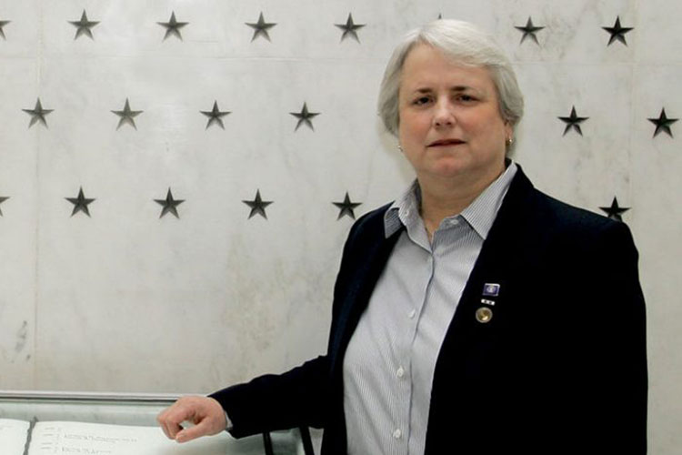 UW alum Helen Noyes poses for a picture at a CIA memorial wall