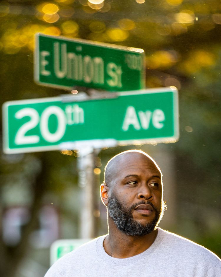 Anthony Washington stands next to street sign