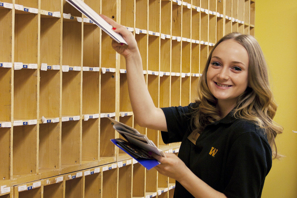 young woman putting letters into office mailboxes