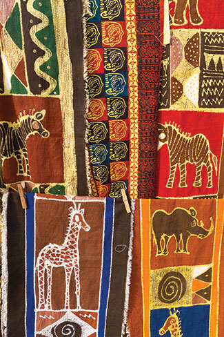 Colorful textiles hanging at a craft village in Zambia feature images of giraffes and zebras, wildlife that tourists to the country are likely to see. The textiles are hand painted by local artists.
