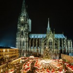 Holiday market booths lit at night in Cologne, Germany