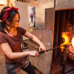 Woman getting molten glass from the kiln