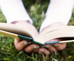 Closeup of hands holding an open book on the grass