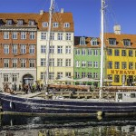 Crowds of people sitting, walking, chatting and relaxing on the picturesque waterfront of Nyhavn, its brightly coloured historic houses, cafes, bars, restaurants and nightclubs reflecting in the tranquil blue waters of the harbour canal leading to Kongens Nytor.