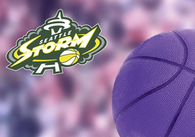 Seattle Storm logo over blurry purple spectators and purple basket ball