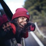 Columbia Sportswear girl wearing a red knitted hat with Columbia logo on the front