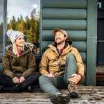 Columbia Sportswear two people sitting in front of a log cabin