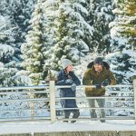 Man and woman leaning on bridge railing in front of snowy trees